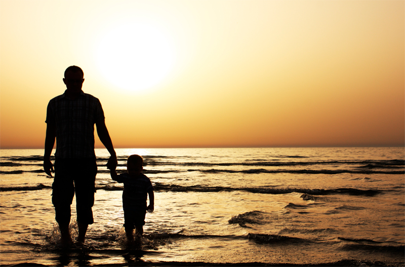 father and son walking along beach